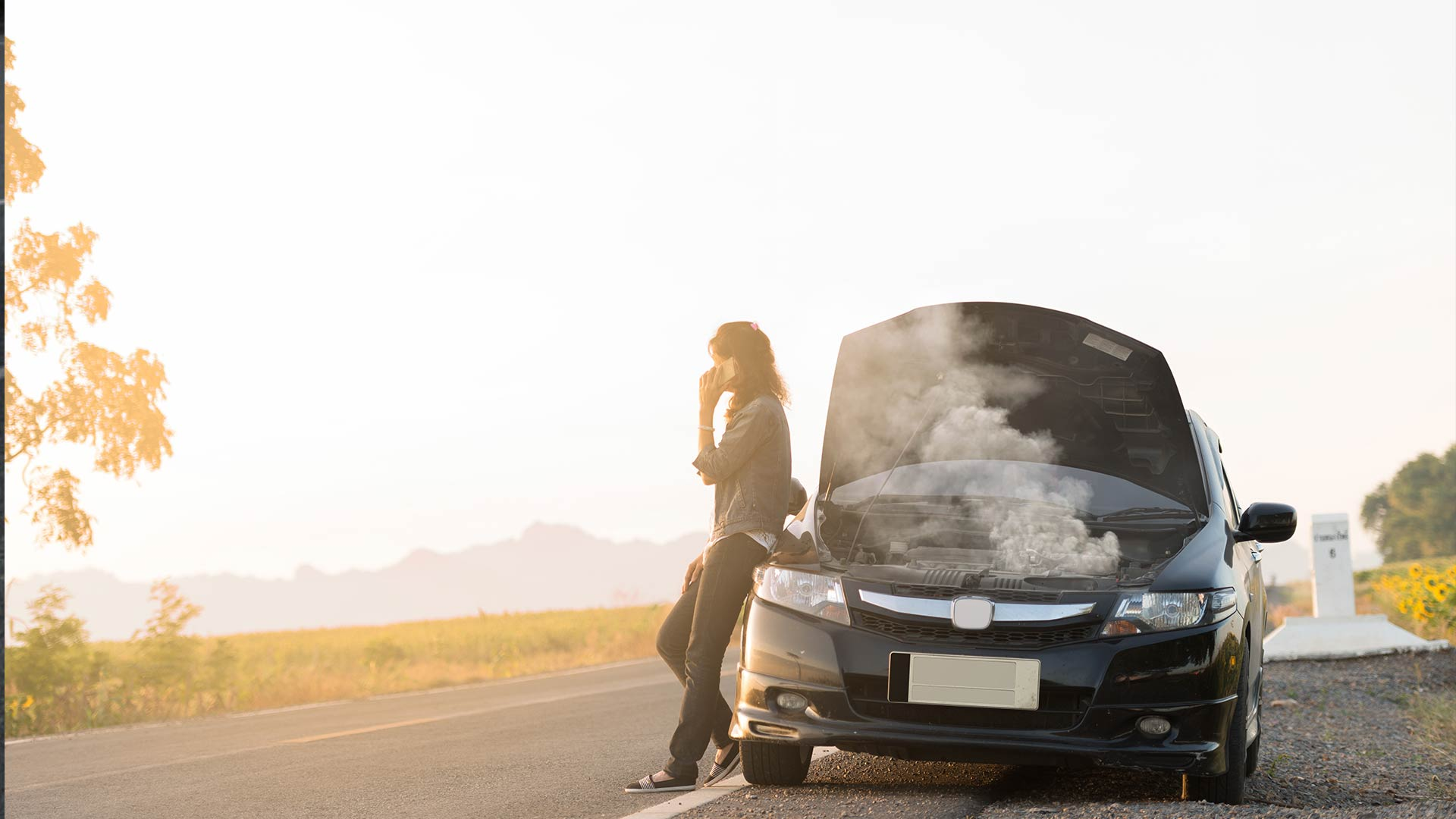 Woman standing by a broken down car